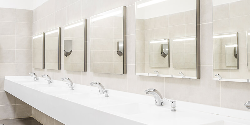 Plombier Expert | Commercial white bathroom with mirrors
