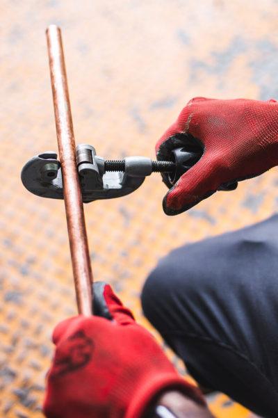 Plombier Expert | Homme avec gants rouges coupant un tuyaux