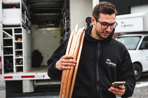 Plombier Expert | Homme à l'extérieur devant un camion et tenant des tuyaux et son cellulaire