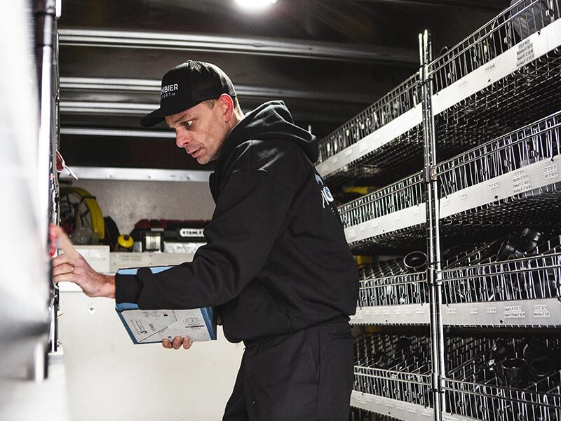Plombier Expert | Employé dans camion mettant à jour l'inventaire
