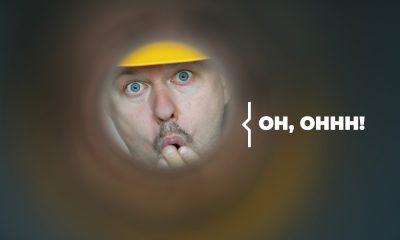 Plombier Expert | Homme avec casque jaune regardant dans un trou